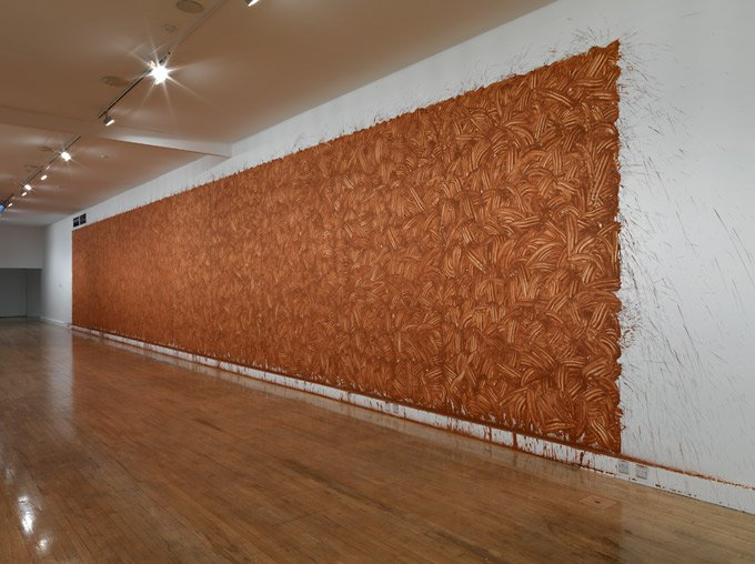 Richard Long From Beginning to End 2009 a wall covering in brown mud which has been applied by had and you can see the hand prints