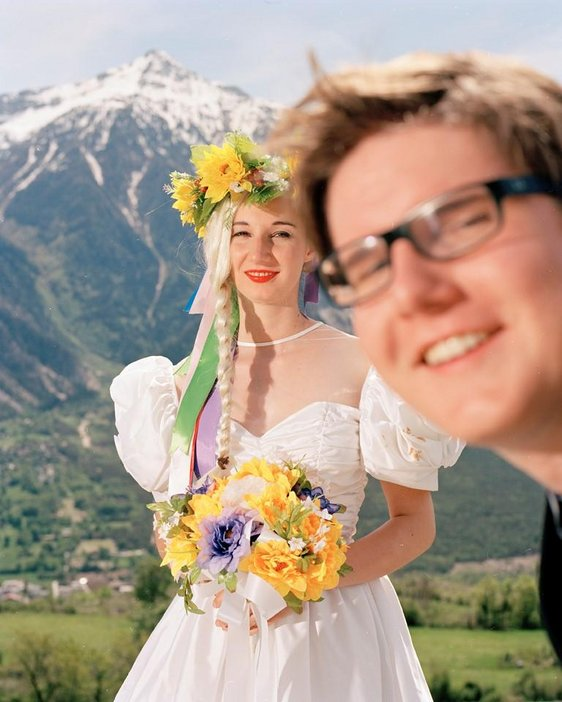 A colour photograph of woman in a wedding dress appears against a mountain background with a person photobombing in front