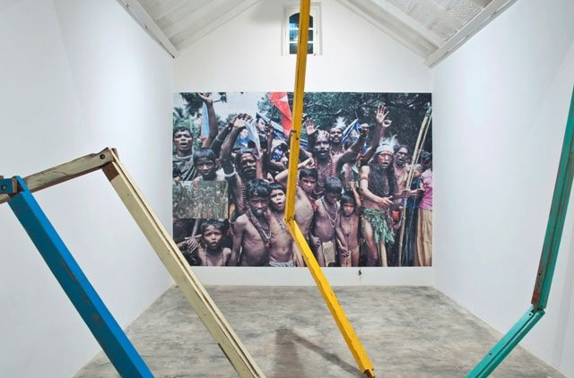 A large photograph on the back wall of the gallery is obscured by coloured wooden pieces of wood stretching from floor to ceiling.