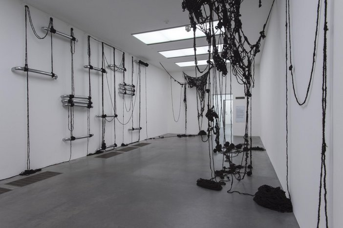 Installation shot showing strings of black human hair draping from the walls and ceiling in a gallery space at Tate Modern