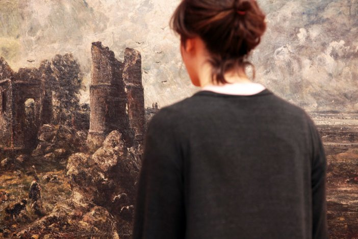 A visitor looking at a Constable painting