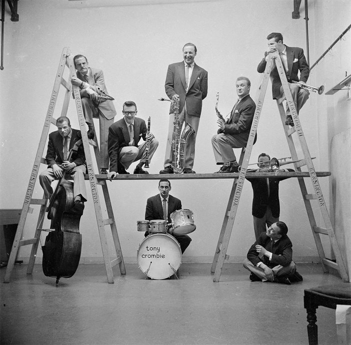 black and white photograph of a band on and around ladders, about 1949 to 1956