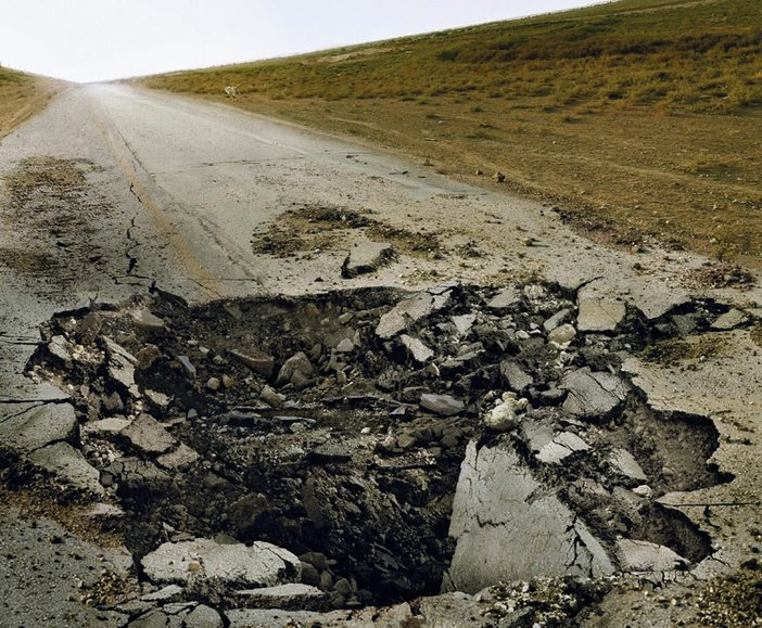 Sophie Ristelhueber Eleven Blowups 1 2006 photograph of a road where a middle section has been destroyed