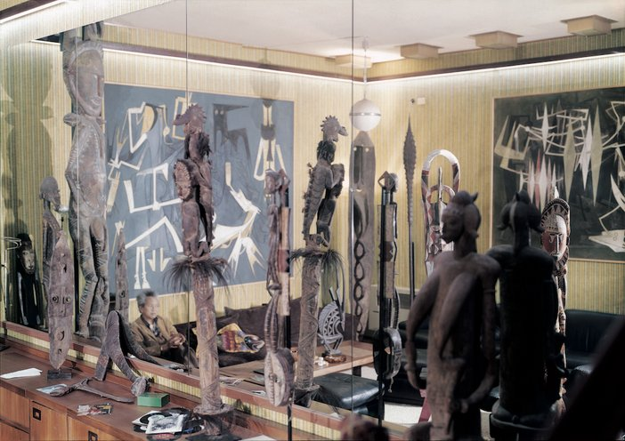 Wifredo Lam surrounded by his collection of African and Oceanic sculptures in the music room in Albissola, 1974