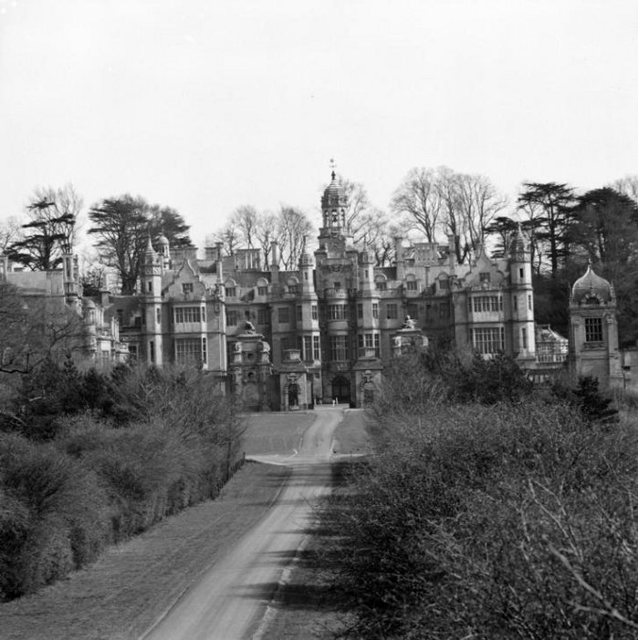 Black and white photograph of huge manor with turrets at the end of a driveway.