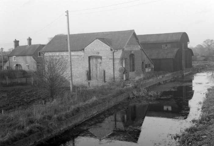 Black and white photograph of a cottage right next to a canal.
