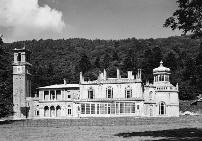 Black and white photograph of a large white manor house with a tower on its left side. This is set against a forest backdrop.