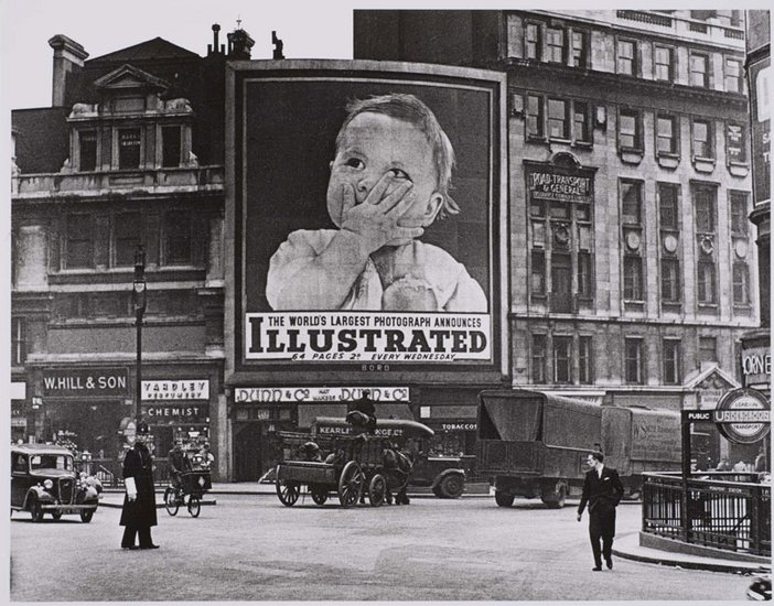 A black and white photograph of a tube station and a large poster of a baby