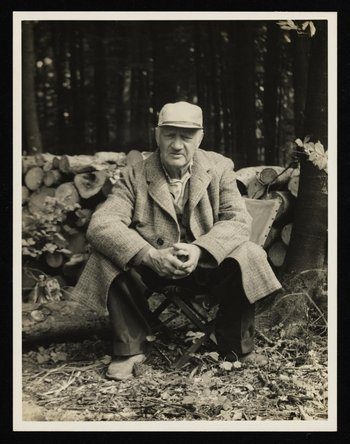 A black and white photograph of Jacob Epstein - he is sitting on a stool with a forest in the background