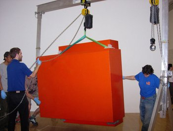 Art Handlers positioning the red box element during installation.