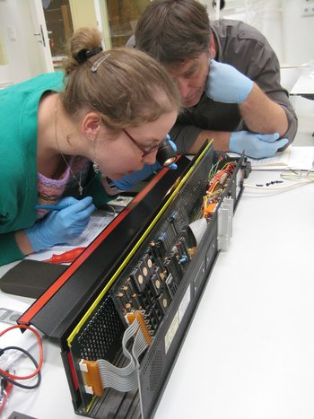 Two conservators examining a black box of electronics
