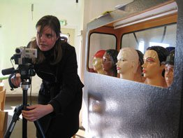 A student using a film camera, with her back to mannequin model heads