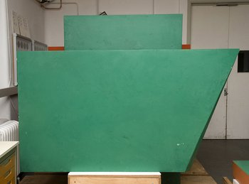 Patchy, whitish degraded coating and paint losses on the green box element of the sculpture.