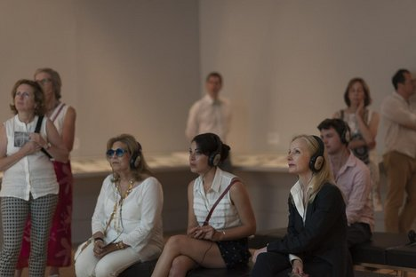 A group of patrons look ahead with headphones in Tate Britain gallery