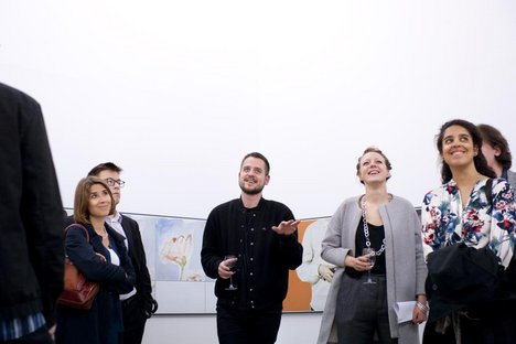 A group of young patrons with artist Nicolas Deshayes look at his exhibition