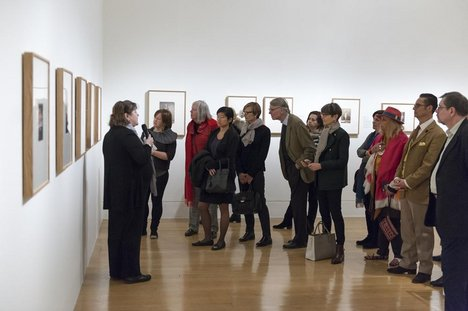 A group of patrons listen to a curator discuss the works in Salt and Silver exhibition