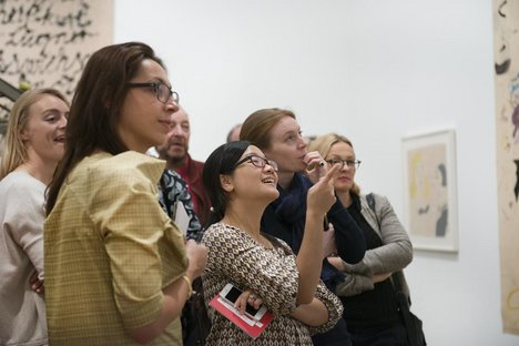 A group of patrons look and admire work in Alibis: Sigmar Polke 1963–2010