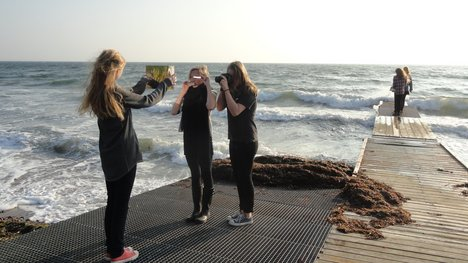 Three students taking photographs on the beach for a Turbinegeneration workshop