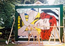 Roy Lichtenstein poses for the camera in front of Girl at Window (1964), made for the New York World's Fair, Flushing Meadows