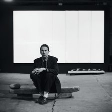 Photograph of Robert Rauschenberg seated on Untitled (Elemental Sculpture) with White Painting (seven panel) behind him at the basement of Stable Gallery, New York 1953