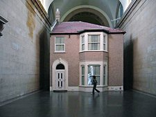 Video still of spectators looking at Michael Landys installation Semi detached at Tate Britain