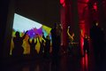 Audience dance in front of digital artwork by Memo Akten