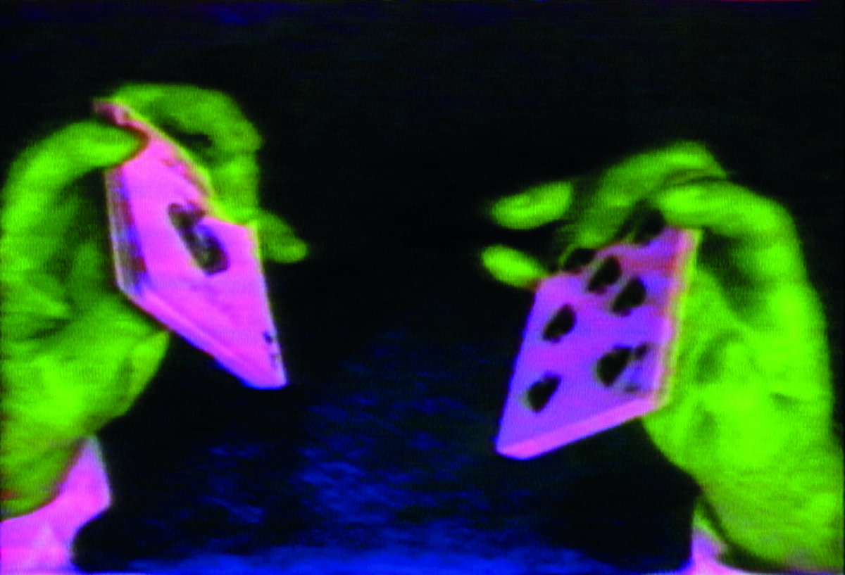 Picture of two green hands holding two pink playing cards