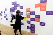 Person adds to an internet timeline mural at the Lives of Net Art event at Tate Exchange