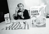 Black and white photograph of Warhol eating cereal