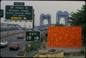 Keith Haring standing next to his Crack is  Wack billboard