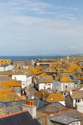 photo of rooftops in St Ives with view out to the sea and sky