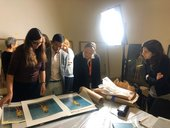 A group of people looking at prints by Rineke Dijkstra on a tabletop with a bright studio light behind