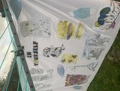 A piece of white fabric hanging from a washing line with a collage of images