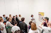 a woman stands in front of a Guerrilla Girls artwork and speaks in front of a crowd in Tate Modern gallery