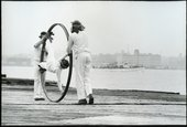 Two figure in white push a large hoop containing another figure in white