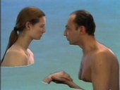A topless man and woman face each other; behind them, a blue-green sea