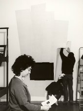 Black and white photo, a person in the foreground looks down at a piece of paper, two people in the background are adhering paper to a gallery wall