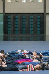 a group of people lying down on Turbine Hall's floor