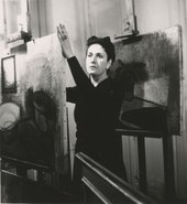 Black and white photograph of the artist Dora Maar standing by an easel