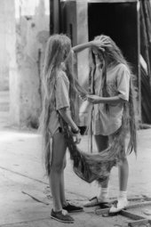image of two young twin girls attached to each other by their long hair