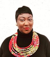 Portrait of Lady Phyll wearing a black shirt and red necklace