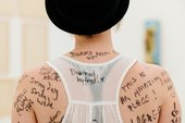 A participant shows viewers text written on her back