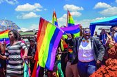 A colour photo of a group of people waving rainbow flags