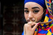 a woman with a beard stares at the camera whilst wearing Indian jewellery