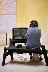 visitor sat on a bench wearing headphones and watching artwork on a tv screen