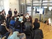A group of people gather around a table, some of using laptops, listening to a workshop leader, behind whom is a screen displaying their own laptop screen for the audience