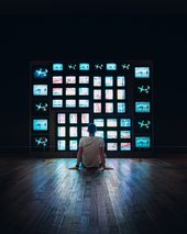 person sat in front of stacked grid of tvs in a dark room