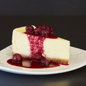 a slice of cheesecake with cherries on top
