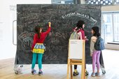 Kids draw on a blackboard with their parent.