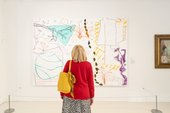 a person looks at an artwork by Rose Wylie with their back to the camera
